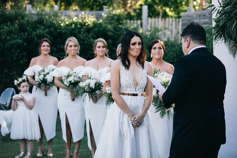 modern wedding ceremony with plunging neckline wedding dress and all white bridesmaid dresses
