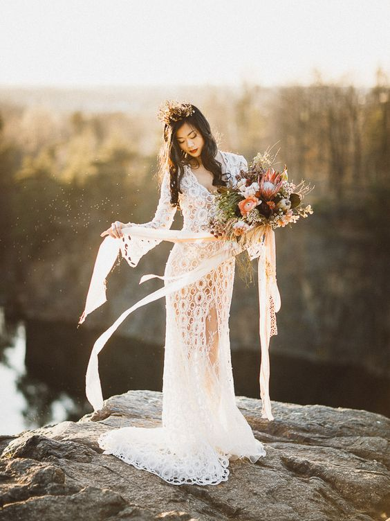 a boho lace sheath wedding gown with bell sleeves, a V-neckline and a front slit for a boho bride