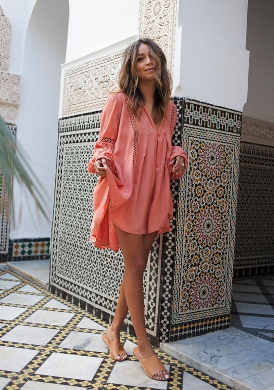 a coral mini dress with long sleeves and decorative holes looks very tropical-like