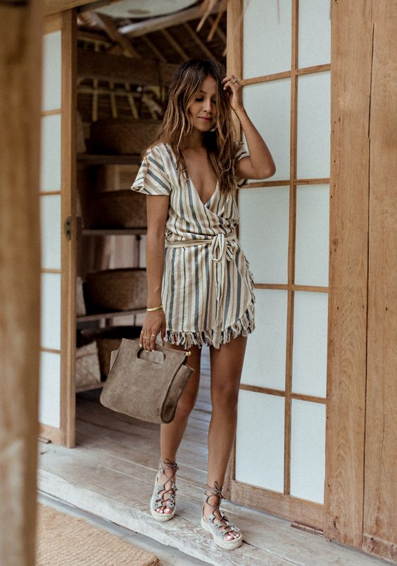 a striped boho romper with a deep V-neckline and lace up shoes