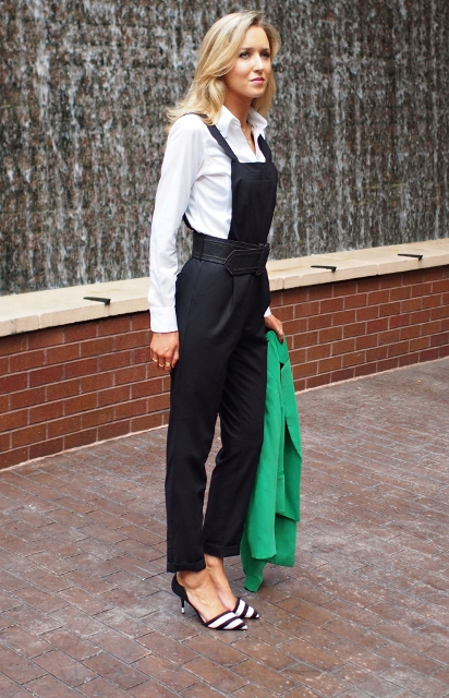 With black jumpsuit, white shirt and green jacket