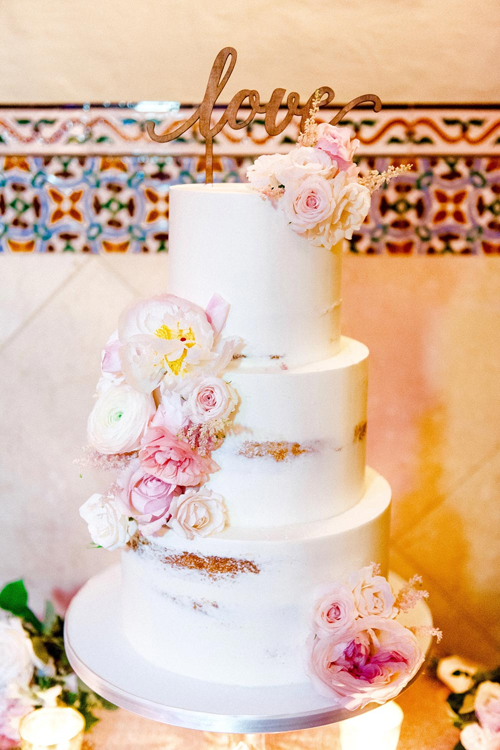 semi-naked buttercream cake with peony toppers