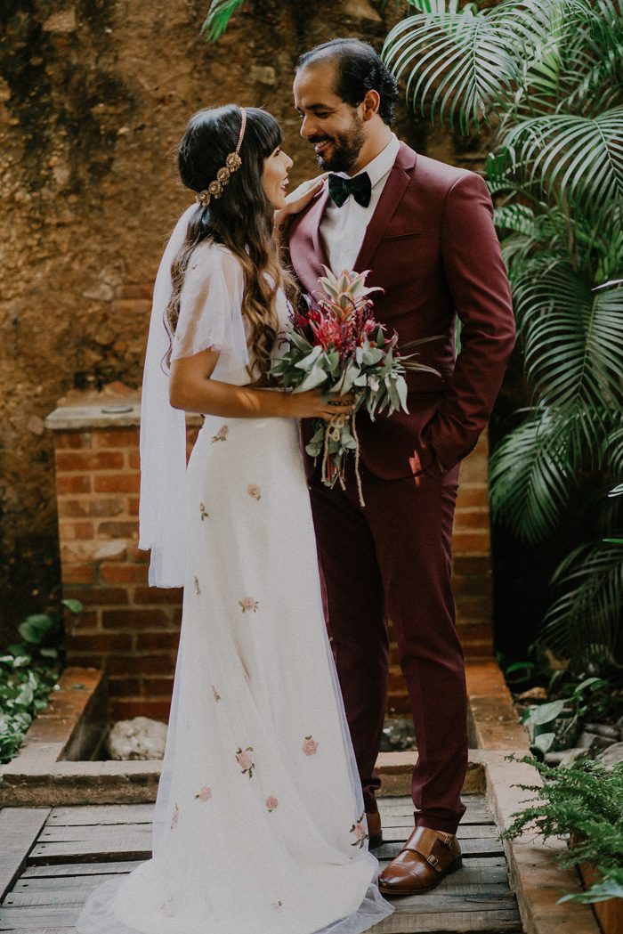 a burgundy suit, a black velvet bow tie, amber-colored shoes for a tropical groom