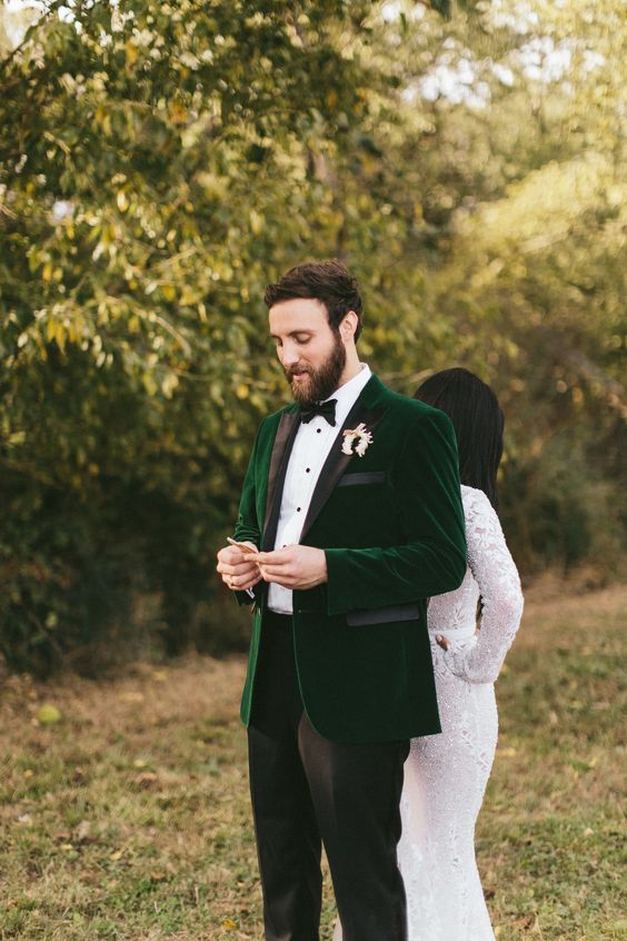 an emerald velvet jacket with black touches, black pants, a bow tie and a white shirt with black buttons