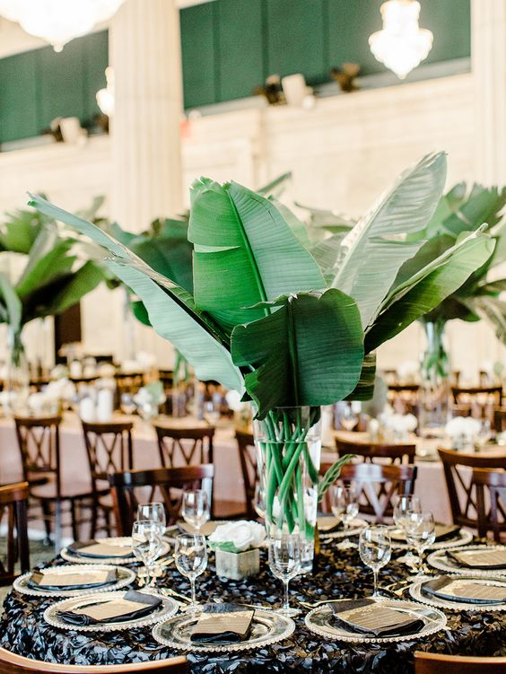 a modern centerpiece with large banana leaves and a clear vase - DIY them all