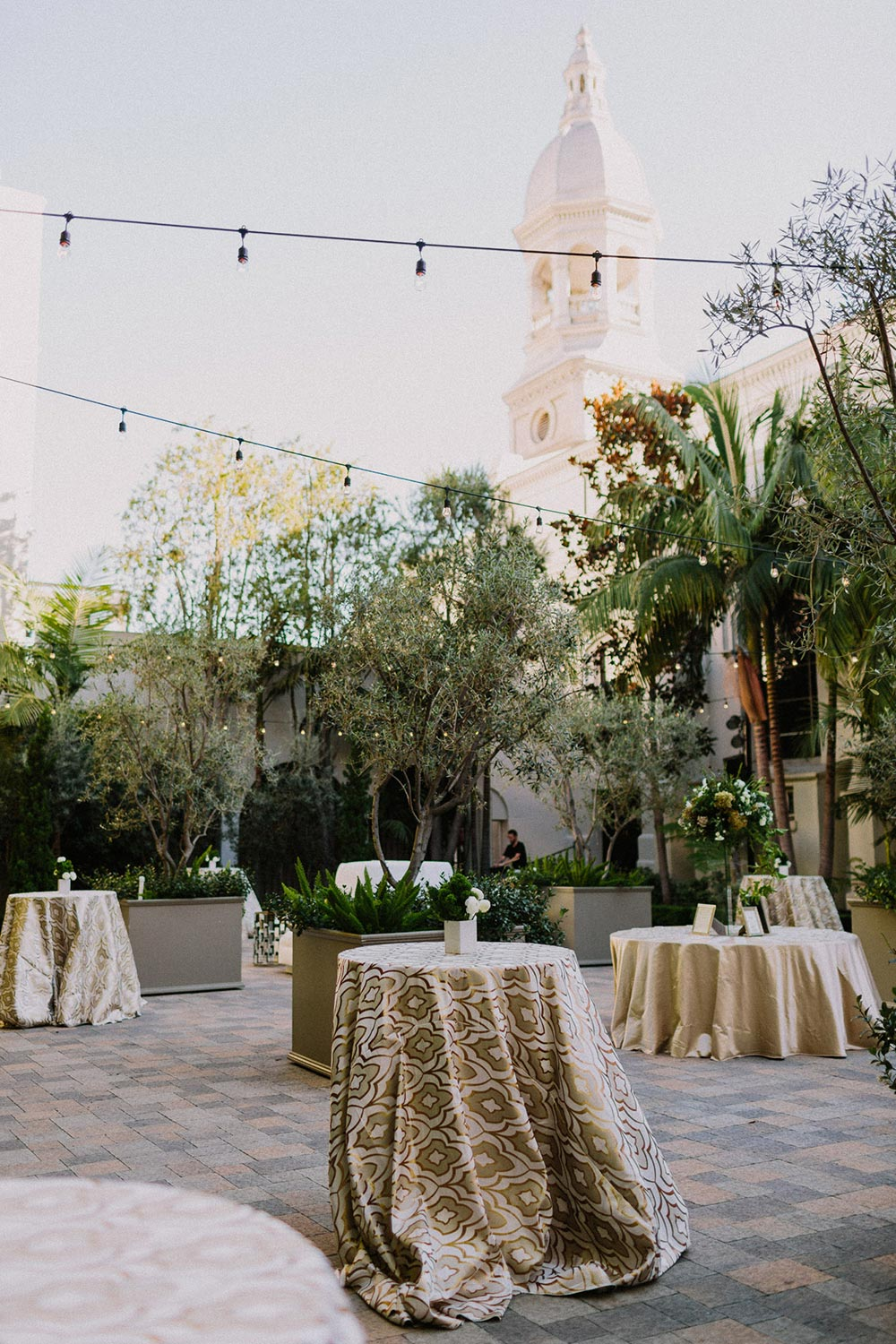 outdoor wedding cocktail hour with market lights and warm linens