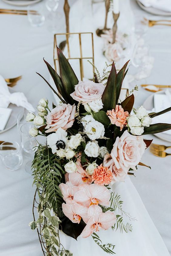 a tropical wedding centerpiece of roses, anemones, orchids and greenery and leaves