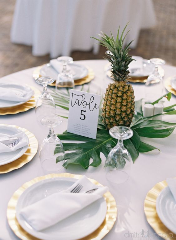 a tropical wedding centerpiece made of a large tropical leaf and a pineapple, you won't need more