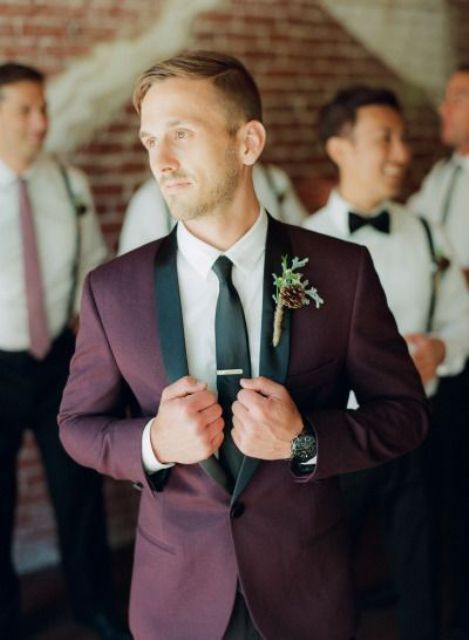 a burgundy tuxedo with black lapels and a black tie for a colorful touch