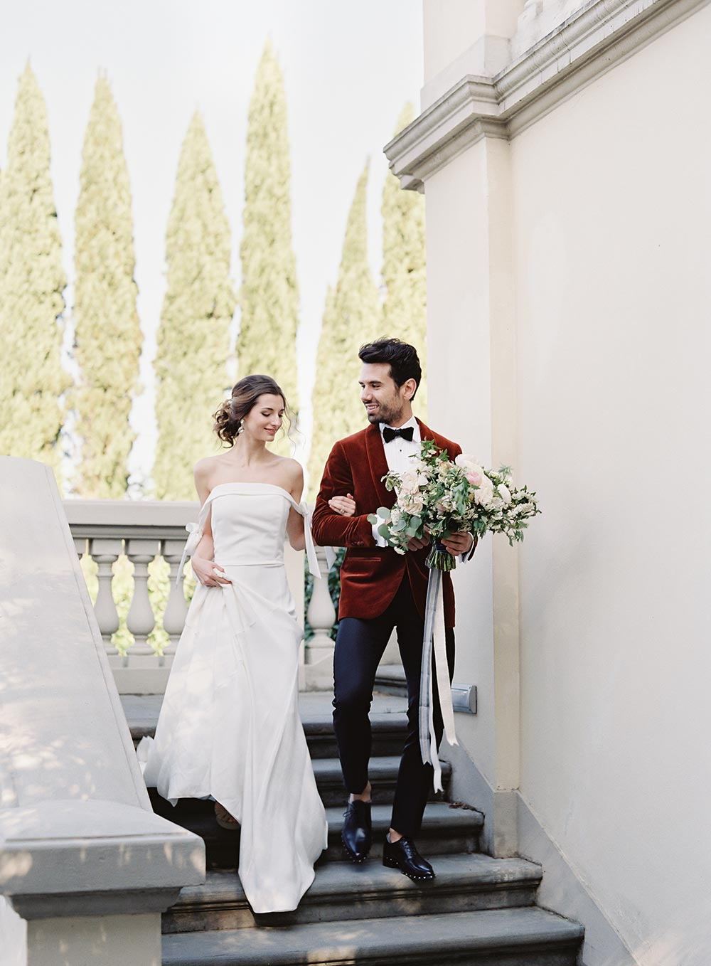 off-the-shoulder wedding dress and burnt orange velvet groom suit