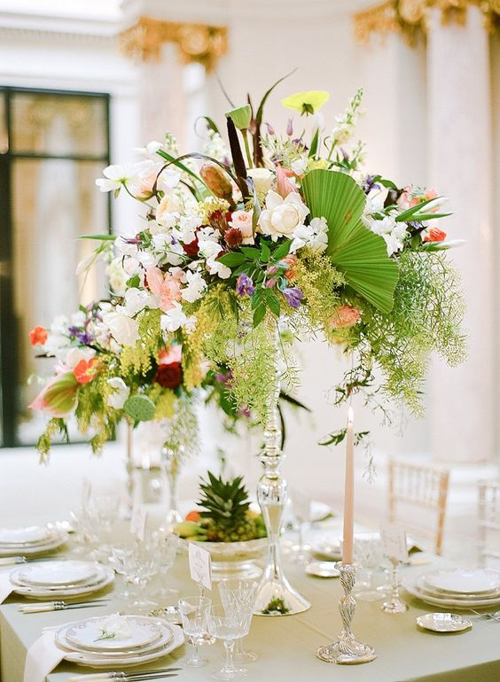 a tall super lush tropical wedidng centerpiece with greenery and all kinds of blooms in light colors
