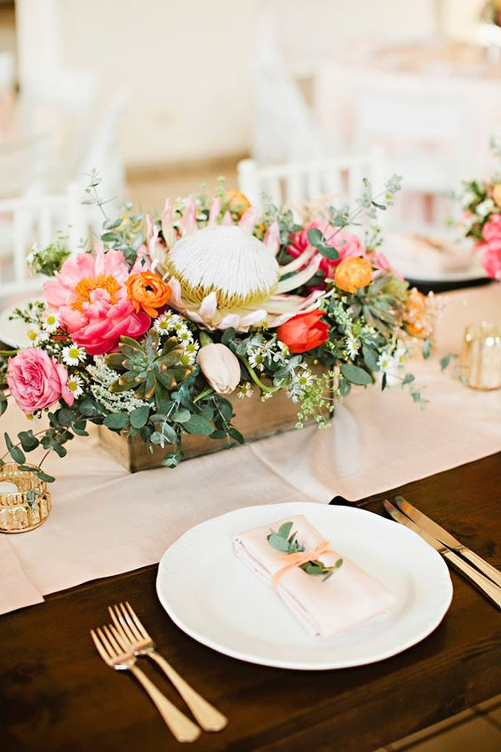a box centerpiece with pink and red blooms, greenery, succulents and a king protea