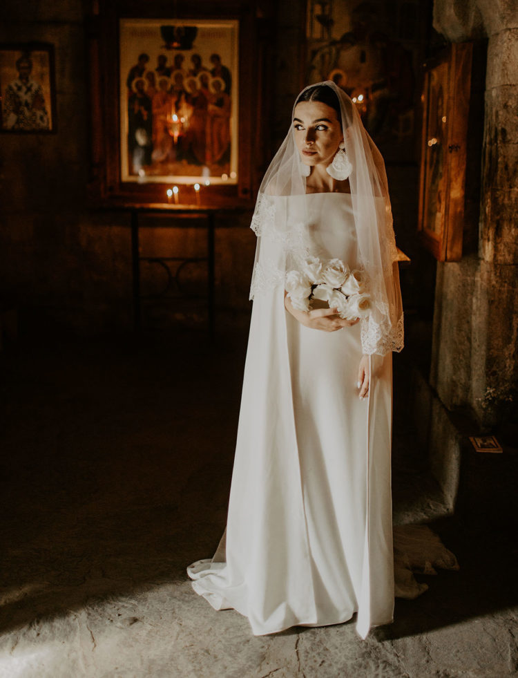 a modern off the shoulder dress with long sleeves with a small train, a veil and statement earrings to add a chic touch