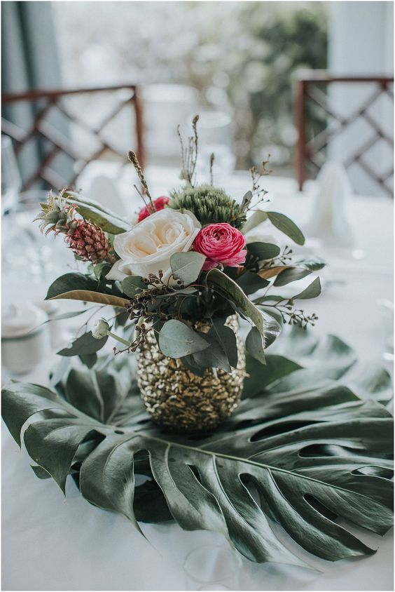 a cool centerpiece of a gilded pineapple, white and pink blooms, greenery and a little pineapple
