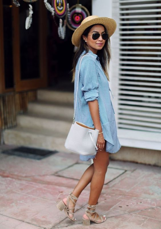 a chambray mini dress, a white bag, tan strappy heels and a hat comprise a cool relaxed look