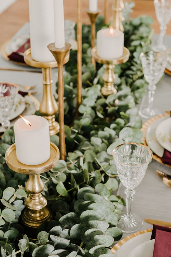 a lush eucalyptus table runner with gold candle holders and pillar candles for a timelessly elegant look