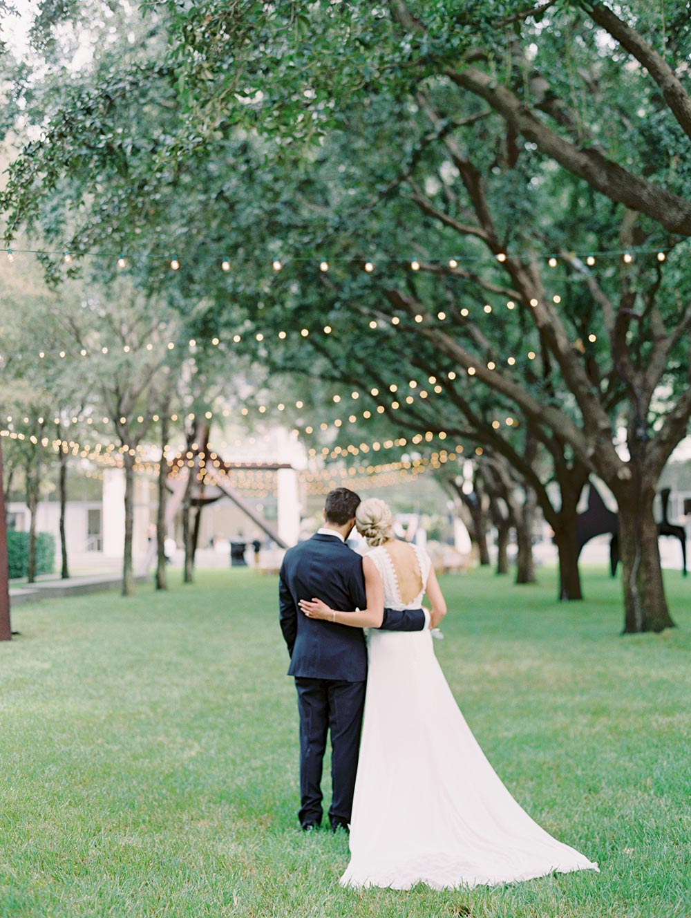 modern lace embroidered wedding dressed navy groom tux string light reception