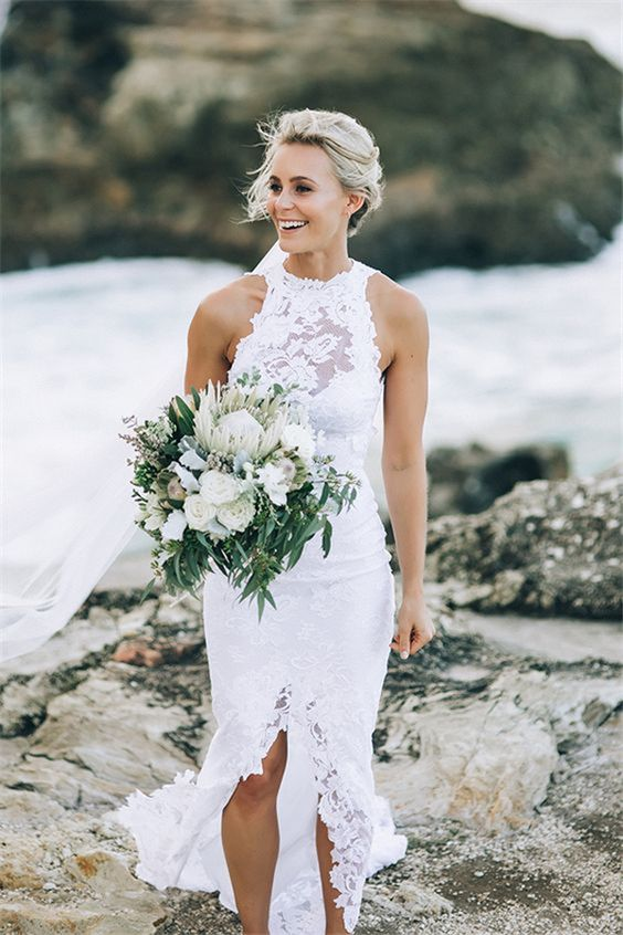 a white lace sheath wedding dress with an illusion neckline and a front slit for a sexy look