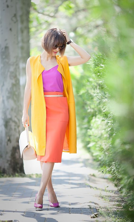 a hot pink top and shoes, an orange midi skirt, a long yellow vest and a creamy bag