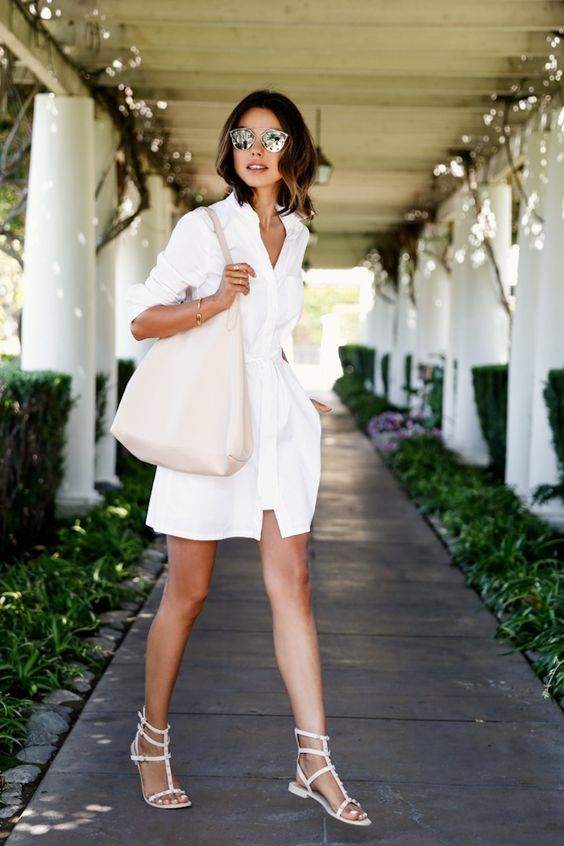 a white short shirtdress, white strappy sandals and a blush bag for a chic look