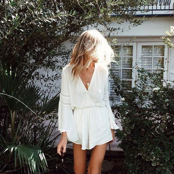a white lacey beach romper with bell sleeves is ideal for a boho chic look