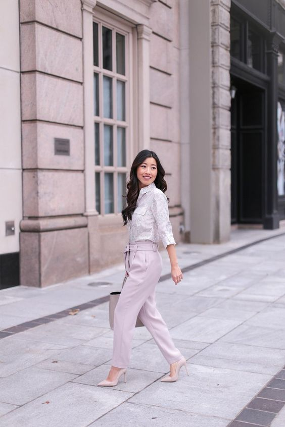 a light-colored floral shirt, pink pants, nude shoes and a bag