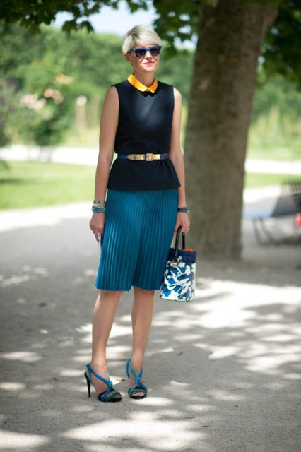 With black top, pleated skirt, high heels and printed bag