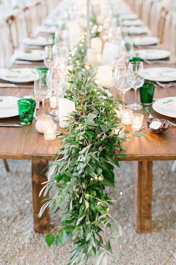a lush greenery table runner with some berries is ideal for a summer woodland wedding