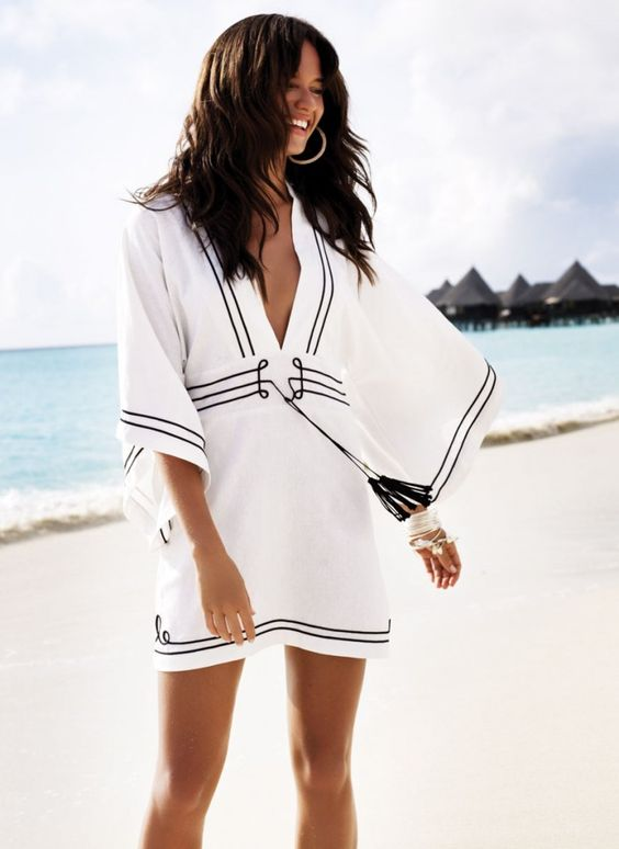 a bold beach tunic with a plunging neckline, bell sleeves and black detailing plus tassels