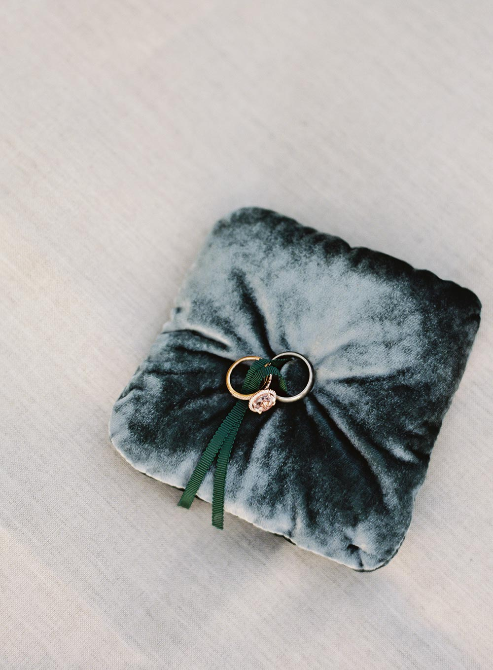 oval rose gold engagement ring with halo and deep teal velvet ring pillow