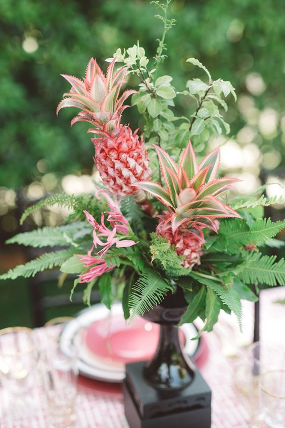 a lush tropical centerpiece of ferns, greenery and pink pineapples looks super cool
