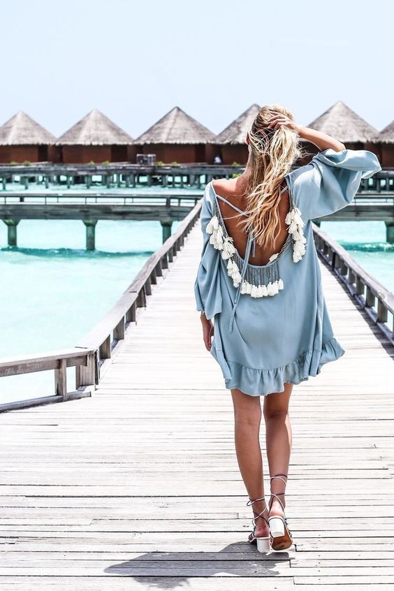 a powder blue tunic with bell sleeves, a cutout back with lacing and multiple tassels