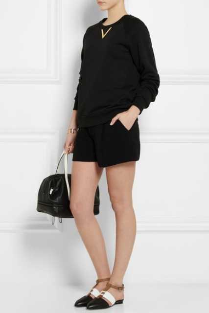 With black shirt, black shorts and white and black bag