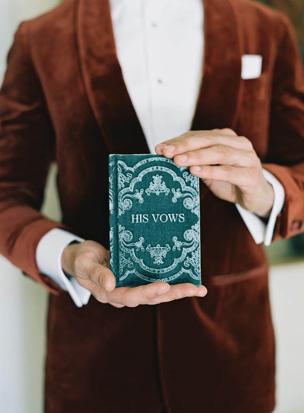 burnt orange velvet groom suit with velvet teal vow book