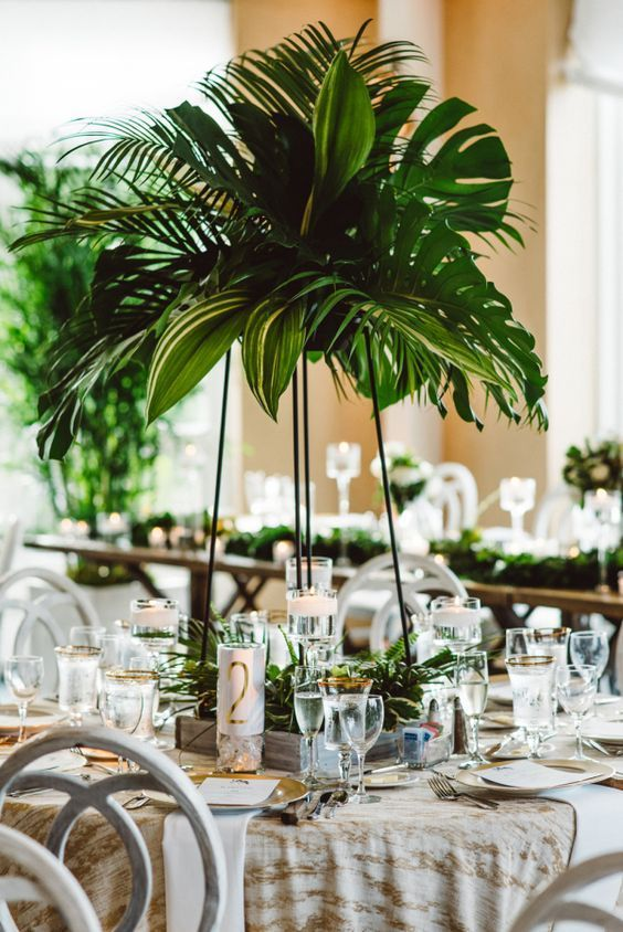 a tall wedding centerpiece with lush tropical greenery and some matching leaves at the base