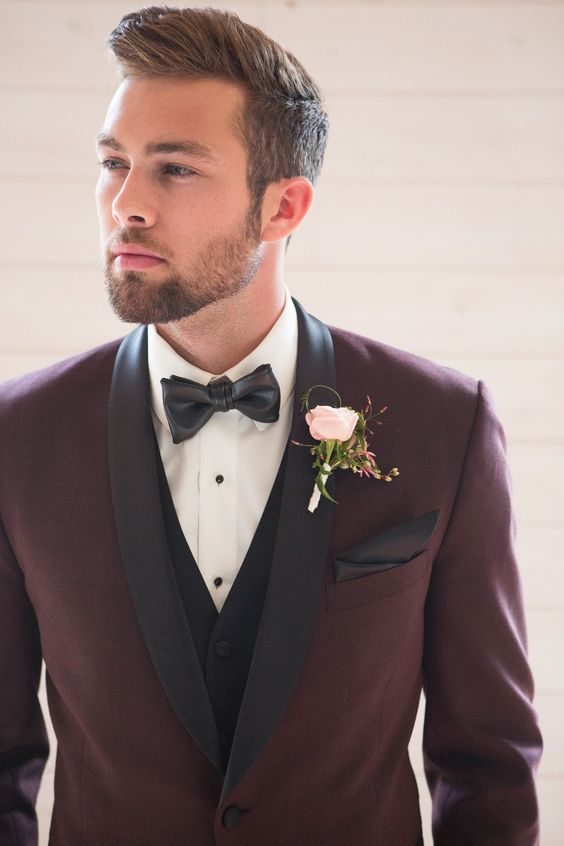 a stylish take on a tuxedo look - a burgundy tux with black lapels and a black vest