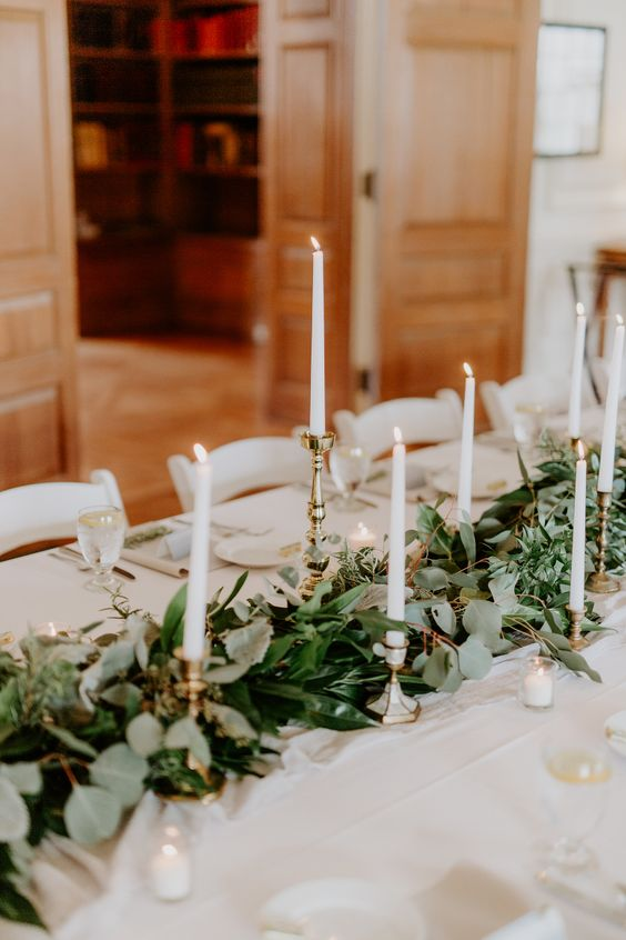 a chic textural foliage table runner with tall candles in gilded candle holders