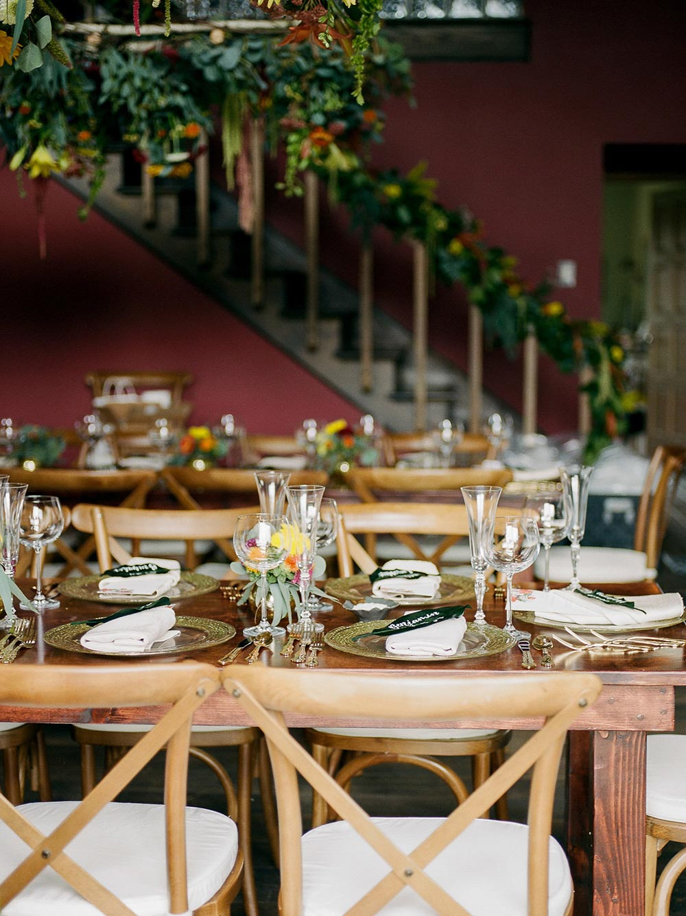 indoor wedding reception with farm tables and suspended greenery