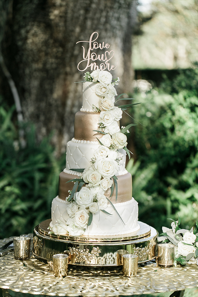 The wedding cake was a gold and white one topped with white ross and a calligraphy topper