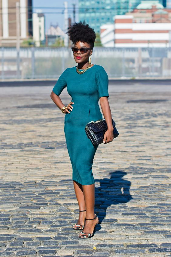 a bold teal fitting midi dress with short sleeves, printed shoes and a clutch