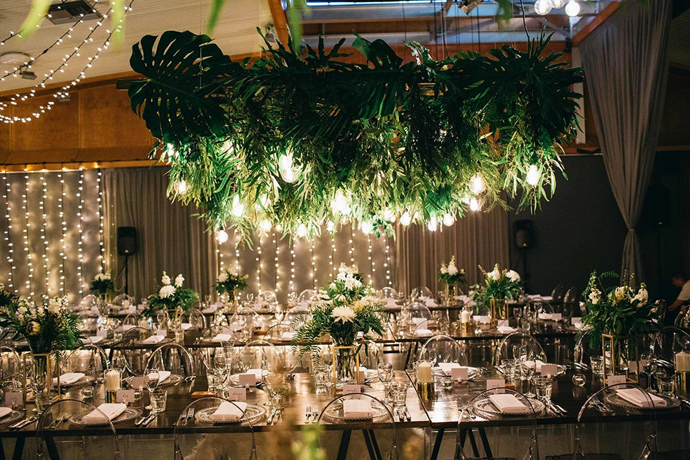 industrial wedding reception with suspended greenery, twinkle lights and lucite chairs