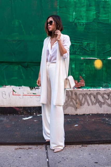 With white button down shirt, white long cardigan, pumps and small bag