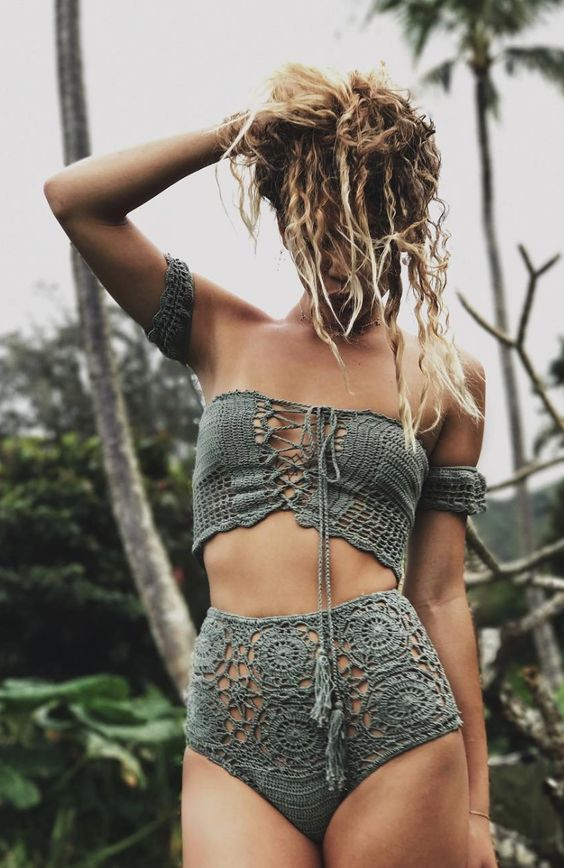 a pale green crochet swimsuit with an off the shoulder lace up top and a high waisted bottom