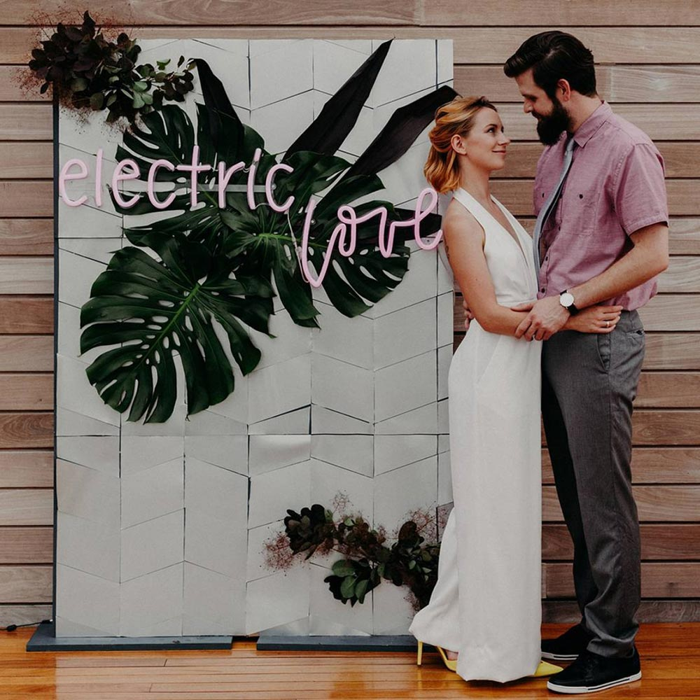 electric love neon wedding signage with tropical backdrop