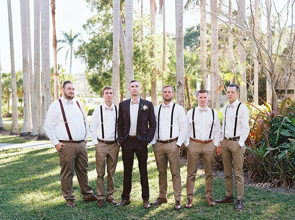 maroon groom suit with floral bow tie and khaki groomsmen attire