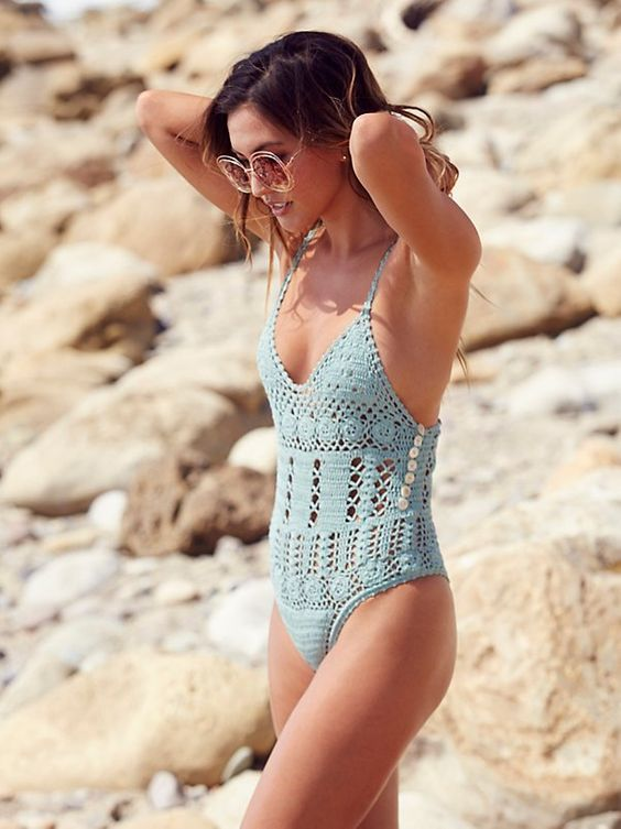 an aqua crocheted one piece swimsuit with buttons and spaghetti straps