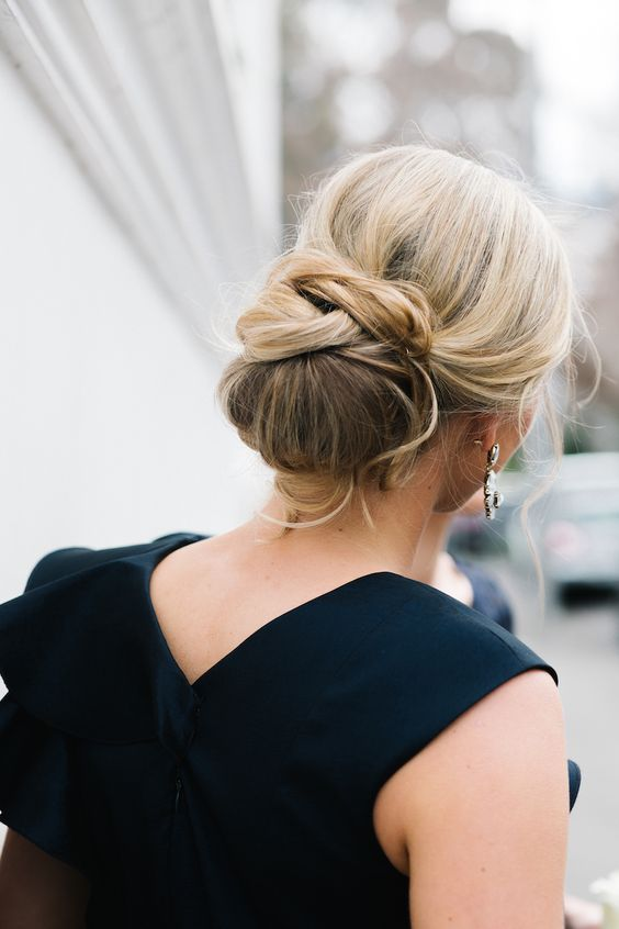 a creative low chignon hairstyle with some twists and curled bangs for a chic look