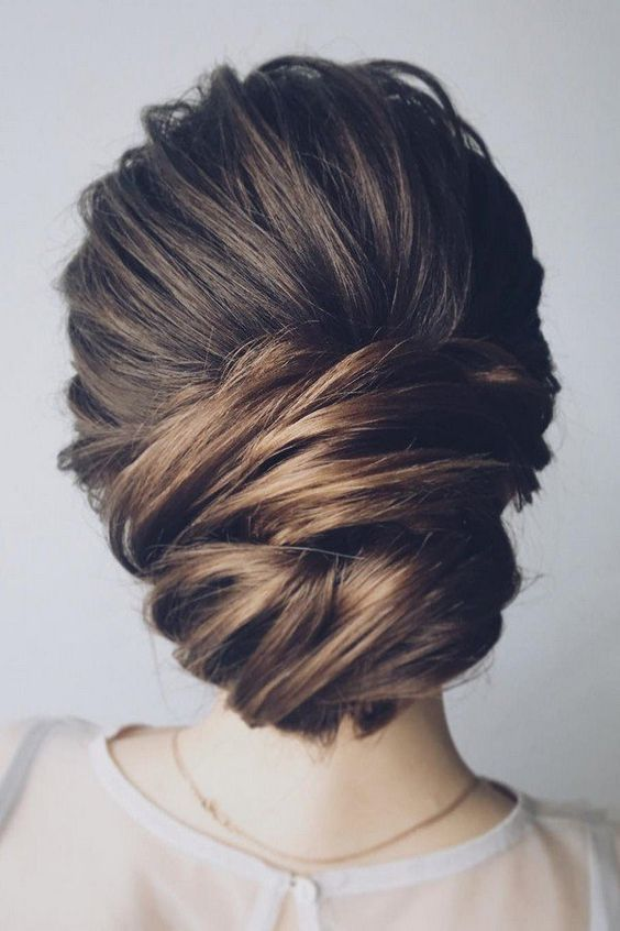 a chic low updo with a bump and much volume and texture for a feminine feel