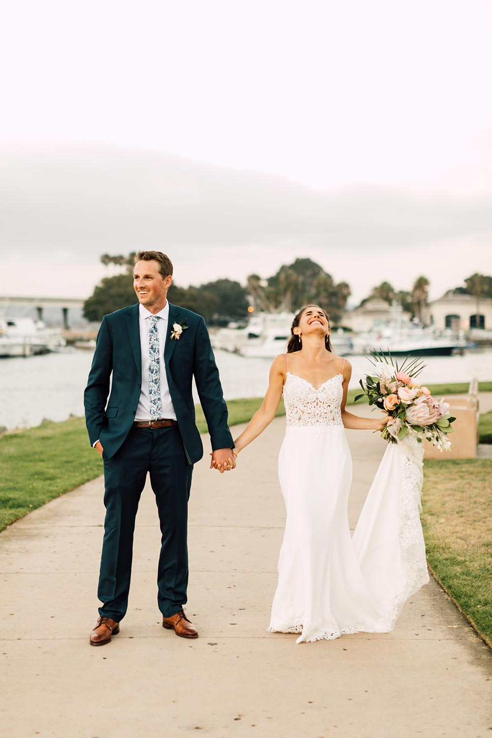 embroidered spaghetti strap wedding dress with navy groom suit and printed floral tie