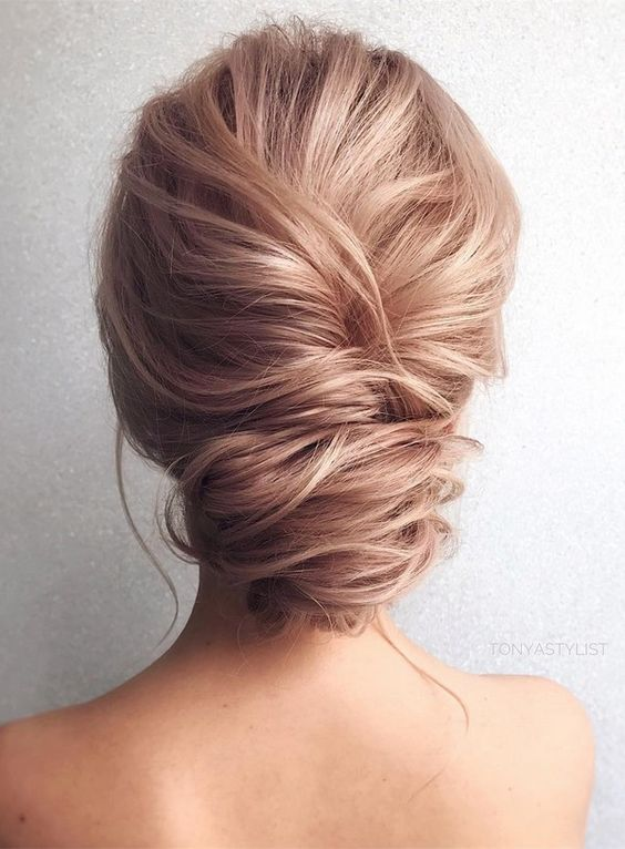 a French twist low updo with a messy look and texture for an elegant yet effortless look